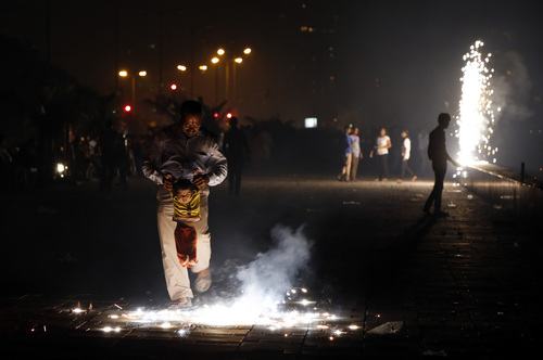 An Indian man holds his son to looks at fireworks as they celebrate Diwali, the Hindu festival of lights, in Mumbai, India, Tuesday, Nov. 5, 2013. Hindus across the country are celebrating Diwali where people decorate their homes with lights and let off fireworks.(AP Photo/Rajanish Kakade)
