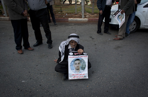 """An elderly Palestinian man holds a poster with a picture of late former prisoner Hassan Turabi, with his name and Arabic that reads, """"condolences to the victim of medical neglect,"""" while taking part in a protest in solidarity with Palestinian prisoners held in Israeli jails, in the West Bank city of Ramallah, Tuesday, Nov. 5, 2013. (AP Photo/Nasser Nasser)"""