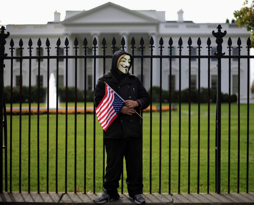 """A demonstrator stands along the fence during a protest in front of the White House in Washington, Tuesday, Nov. 5, 2013, against corrupt governments and corporations, part of a Million Mask March of similar rallies around the world on Guy Fawkes Day. Guy Fawkes Day, Nov. 5,  is to mark when English authorities arrested Guy Fawkes, the leader of the """"Gunpowder Plot"""" during a to blow up Houses of Parliament in 1605.   (AP Photo/Pablo Martinez Monsivais)"""