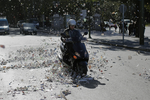 A man drives his motorcycle as papers fly around during the first day of a garbage collectors strike in Madrid, Tuesday, Nov. 5, 2013. Street cleaners and garbage collectors who work in the city's public parks walked off the job at midnight in a strike called by trade unions to contest the planned layoff of more than 1,000 workers. Madrid's municipal cleaning companies, which have service supply contracts with the city authorities, employ some 6,000 staff. (AP Photo/Andres Kudacki)