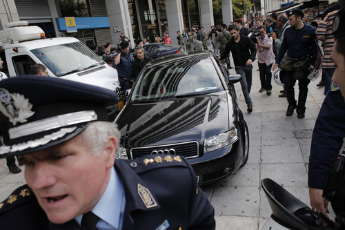 Members of an international debt inspection team are escorted by riot police after exiting through an emergency door during a demonstration at the Finance Ministry in Athens on Tuesday Nov. 5, 2013. Representatives of Greece's bailout creditors were confronted by protesters on the first day of new talks on the financially battered country's austerity program. Armed with a bullhorn, a few dozen civil servants chanted anti-austerity slogans Tuesday outside the room where the officials were meeting Finance Minister Yannis Stournaras. (AP Photo/Dimitri Messinis)