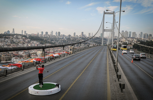 Golf star Tiger Woods of the United States makes a shot from East to West on the iconic Bosporus Bridge that separates the continents of Europe and Asia, in Istanbul, Turkey, Tuesday, Nov. 5, 2013. Woods will compete in the USD7million Turkish Airlines Open in Antalya, Nov. 7-10. (AP Photo)