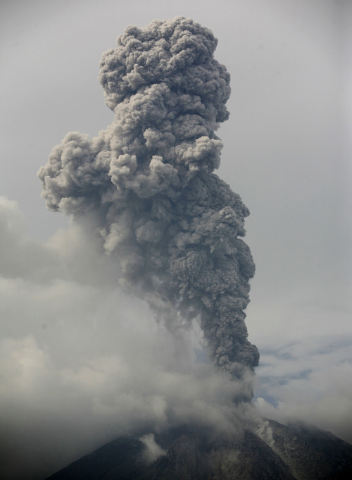 Mount Sinabung spews volcanic materials during an eruption as seen from Tiga Pancur, North Sumatra, Indonesia, Tuesday, Nov. 5, 2013. The 2,600-meter (8,530-foot) -high volcano has been erupting since Sunday, unleashing volcanic ash high into the sky and forcing the evacuation of villagers living around its slope. (AP Photo/Binsar Bakkara)