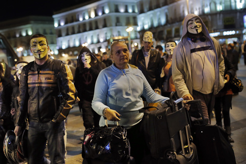 A tourist, centre, stands with her luggage as Spanish activists wearing an anonymous' masks march during a protest against corrupt governments and corporations, in support of the anonymous activist movement, at the Sol square, in Madrid, Spain, Tuesday, Nov 5, 2013, as part of a Million Mask March of similar rallies around the world. (AP Photo/Andres Kudacki)