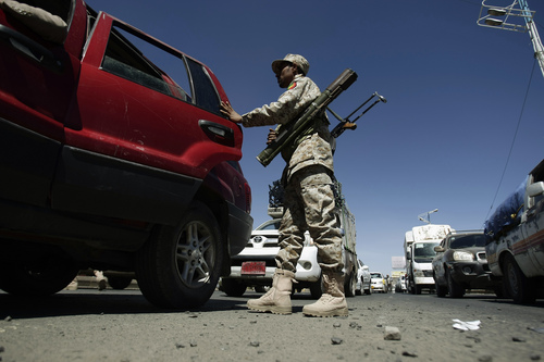 A Yemeni soldier inspects a car at a checkpoint in a street in Sanaa, Yemen, Tuesday, Nov. 5, 2013. A spokesman for an ultraconservative Muslim movement said Monday that clashes between his group and rebels in Yemen's restive north have left four dead, breaking a ceasefire. (AP Photo/Hani Mohammed)