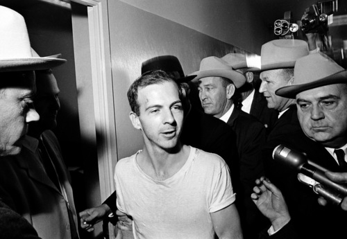 Surrounded by detectives, Lee Harvey Oswald talks to the press as he is led down a corridor of the Dallas police station for another round of questioning in connection with the assassination of U.S. President John F. Kennedy, November 23, 1963. Oswald, who denies any involvement in the shooting, is formally charged with murder. (AP Photo)