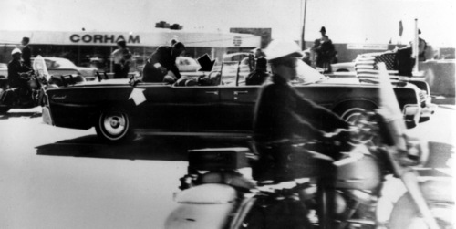 Secret Service agent Clint Hill climbs into the back seat of the limousine a moment after President John F. Kennedy and Governor John Connally of Texas were shot in Dallas, Nov. 22, 1963.  Black arrow points to Mrs. Connally ducking bullets, and white arrow points out the agent's foot, mistakenly thought to be the president's when the photo first ran.  (AP Photo)