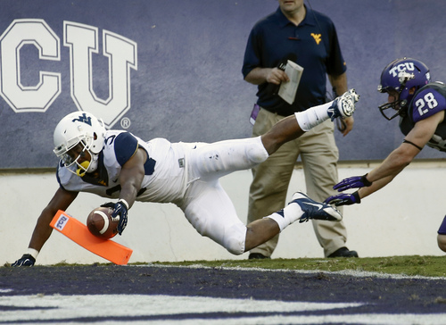 West Virginia running back Charles Sims (3) dives past the goal line scoring a touchdown in front of TCU safety Derrick Kindred (26) during the second half of an NCAA football game, Saturday, Nov. 2, 2013, in Fort Worth, Texas. West Virginia won 30-27. (AP Photo/Jim Cowsert)