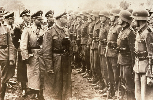 The June 3, 1944 photo provided by the US Holocaust Memorial Museum shows Heinrich Himmler, centre,  SS Reichsfuehrer-SS, head of the Gestapo and the Waffen-SS, and Minister of the Interior of Nazi Germany from 1943 to 1945, as he reviews troops of the Galician SS-Volunteer Infantry Division. (AP photo/ U.S. Holocaust Memorial Museum, courtesy of Atlantic Foto Verlag Berlin)