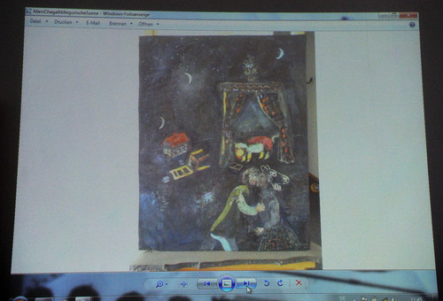 A painting of Marc Chagall is projected on a screen during a news conference in Augsburg, southern Germany, Tuesday, Nov. 5, 2013, on the art found in Munich. A hoard of more than 1,400 art works found last year at a Munich apartment includes previously unknown pieces by artists including Marc Chagall, German investigators said Tuesday, adding that they face a hugely complicated task to establish where the art came from. (AP Photo/Kerstin Joensson)