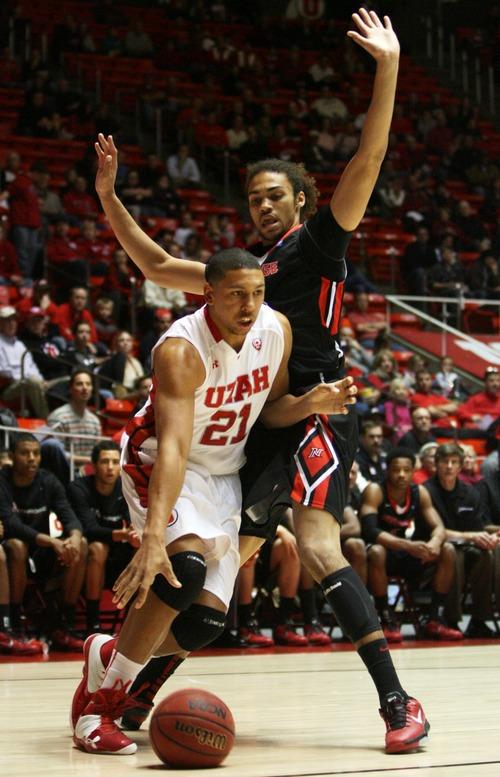Kim Raff  |  The Salt Lake Tribune (left) University of Utah forward Jordan Loveridge (21) drives the basket past Cal State Northridge forward/center Tre Hale-Edmerson (35) during first half at the Huntsman Center in Salt Lake City on December 21, 2012.