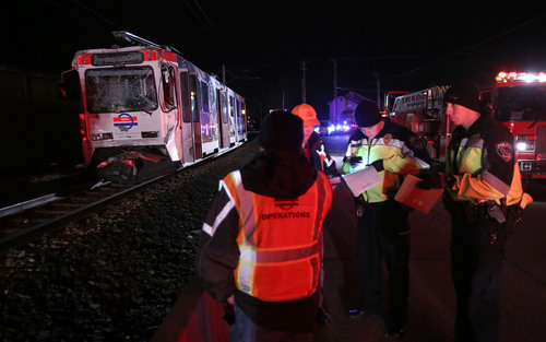 Francisco Kjolseth  |  The Salt Lake Tribune A North bound TRAX train who's last car unbuckled and sat still on the track near 8000 South and State Street in Midvale lies crushed after being rear ended by another North bound train train on Tuesday night, Nov. 5, 2013. The driver of the second train moving up the line a short while later was able to slow down but not avoid the collision.