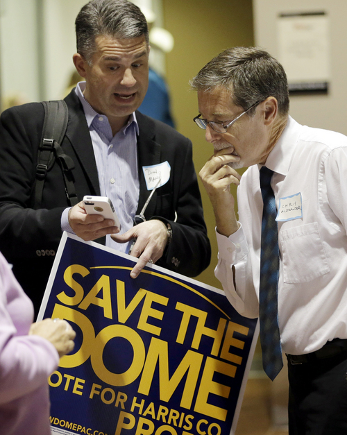 Dinn Mann, left, and Chris Alexander, right, look at early voting results Tuesday, Nov. 5, 2013, in Houston. Houston-area voters are deciding whether to convert the Astrodome into a convention center or allow the stadium to be demolished. (AP Photo/David J. Phillip)