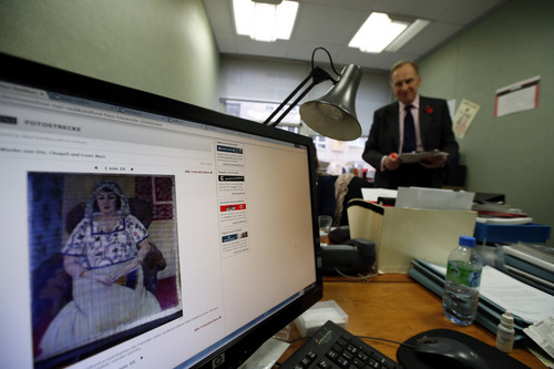 A picture on a news website, showing a painting by Henry Matisse entitled 'Sitzende Frau' ('Sitting Woman') which is part of the art recently found in Munich, Germany, as researchers of the Art Loss Register continue their work at their offices in central London, Wednesday, Nov. 6, 2013, with Julian Radcliffe, centre, chairman of the Art Loss Register. Phones in these London offices have been ringing off the hook since the announcement that German authorities have discovered more than 1,400 artworks, some by modern masters such as Marc Chagall, Henri Matisse and Pablo Picasso, stacked in a Munich apartment. German officials have not revealed details about the vast majority of the paintings, drawings, engravings, woodcuts and prints they have found, sparking a scramble for information on the part of art-hunters and lawyers for those seeking to recover looted art.(AP Photo/Lefteris Pitarakis)