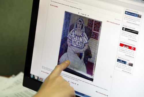 A researcher of the Art Loss Register at their offices in central London, Wednesday, Nov. 6, 2013, points to a picture on a news website, showing a painting by Henry Matisse entitled 'Sitzende Frau' ('Sitting Woman') which is part of the art recently found in Munich, Germany.  Phones in these London offices have been ringing off the hook since the announcement that German authorities have discovered more than 1,400 artworks, some by modern masters such as Marc Chagall, Henri Matisse and Pablo Picasso, stacked in a Munich apartment. German officials have not revealed details about the vast majority of the paintings, drawings, engravings, woodcuts and prints they have found, sparking a scramble for information on the part of art-hunters and lawyers for those seeking to recover looted art.(AP Photo/Lefteris Pitarakis)