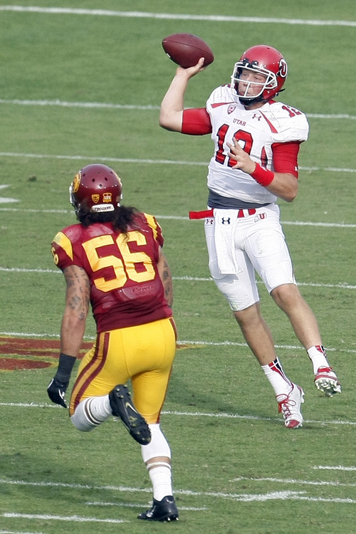 Chris Detrick  |  The Salt Lake Tribune Utah Utes quarterback Adam Schulz (12) passes past USC Trojans linebacker Anthony Sarao (56) during the second half game at the The Los Angeles Memorial Coliseum Saturday October 26, 2013. USC won the game 19-3.