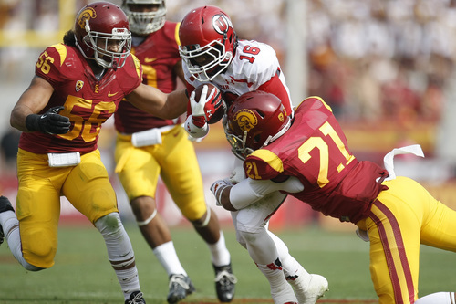 Chris Detrick  |  The Salt Lake Tribune Utah Utes wide receiver Geoff Norwood (16) is tackled by USC Trojans linebacker Anthony Sarao (56) and USC Trojans safety Su'a Cravens (21) during the first half game at the The Los Angeles Memorial Coliseum Saturday October 26, 2013. USC is winning the game 16-3.