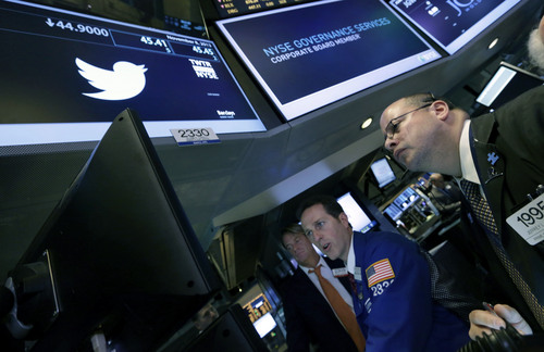 Trader Jeffrey Vazquez, right, and specialist Glenn Carell, center, work at the post that trades Twitter on the floor of the New York Stock Exchange Friday, Nov. 8, 2013. Stocks edged higher in early Friday trading as investors reacted to an unexpectedly strong October jobs report. (AP Photo/Richard Drew)