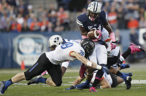 BYU's Jamaal Williams takes a hit from Boise State's Corey Bell during an NCAA college football game, Friday, Oct. 25, 2013 at LaVell Edwards Stadium in Provo, Utah. (AP Photo/The Daily Herald, Mark Johnston)