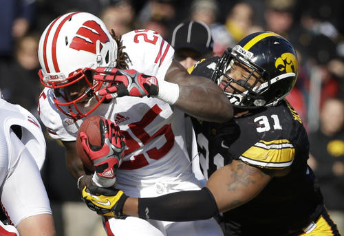 Iowa linebacker Anthony Hitchens (31) tackles Wisconsin running back Melvin Gordon during the first half of an NCAA college football game, Saturday, Nov. 2, 2013, in Iowa City, Iowa. (AP Photo/Charlie Neibergall)