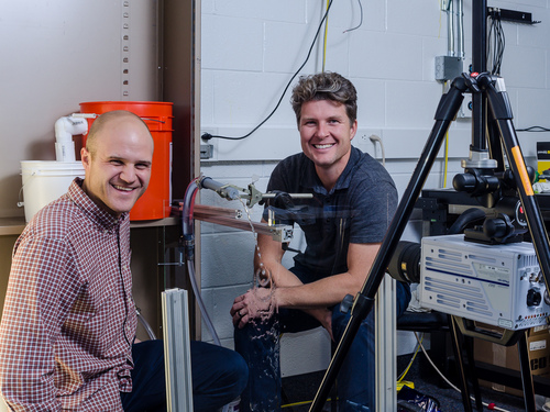 Randy Hund and Tadd Truscott with their urine simulation rig and high-speed camera. The Brigham Young University scientists are presenting their work on preventing male urine splash back later this month.  Courtesy Chris Mabey  |  BYU