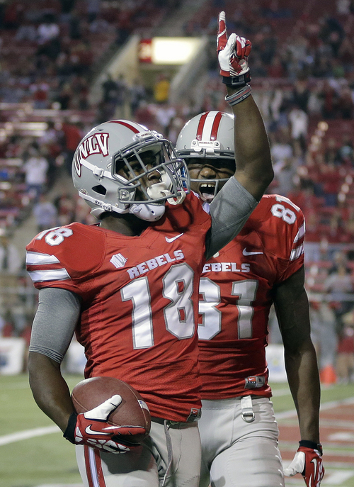 UNLV wide receiver Marcus Sullivan (18) celebrates with wide receiver Devante Davis after scoring a touchdown against Utah State in the first quarter of an NCAA college football game Saturday, Nov. 9, 2013, in Las Vegas. (AP Photo/Julie Jacobson)