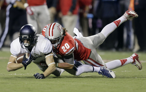 Utah State wide receiver Travis Van Leeuwen, left, is tackled by UNLV defensive back Matt Vinal (20) after catching a pass in the second quarter of an NCAA college football game Saturday, Nov. 9, 2013, in Las Vegas. (AP Photo/Julie Jacobson)