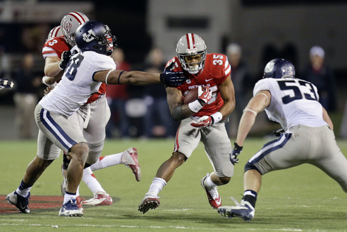 UNLV running back Tim Cornett (35) tries to bring the ball through a hole between Utah State defensive end Paul Piukala, left, and linebacker Zach Vigil (53) in the second quarter of an NCAA college football game Saturday, Nov. 9, 2013, in Las Vegas. (AP Photo/Julie Jacobson)