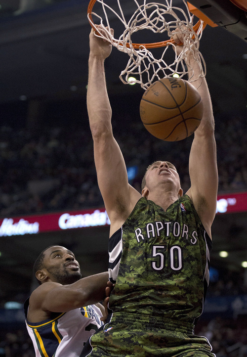 Toronto Raptors forward Tyler Hansbrough (50) dunks the ball against Utah Jazz forward Mike Harris during the first half of an NBA basketball game in Toronto on Saturday, Nov. 9, 2013. (AP Photo/The Canadian Press, Frank Gunn)