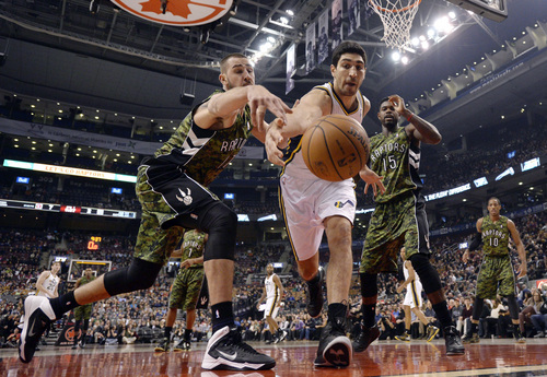 Utah Jazz center Enes Kanter, center, battles Toronto Raptors center Jonas Valanciunas, left, for the ball during the first half of an NBA basketball game in Toronto on Saturday, Nov. 9, 2013. (AP Photo/The Canadian Press, Frank Gunn)