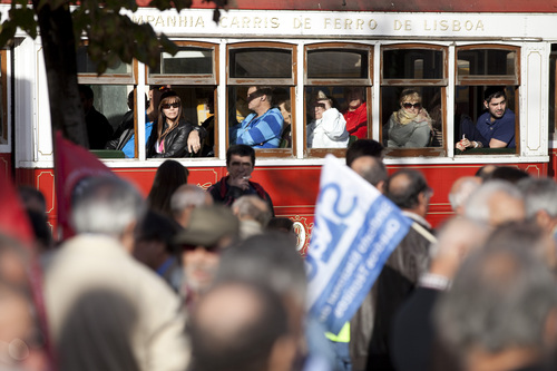 Tourists riding a Lisbon tour tram watch demonstrators gathering for a transport workers protest march in Lisbon, Saturday, Nov. 9 2013. A few hundred took part in the march as labor groups continue their battle against pay and pension cuts and the loss of entitlements. (AP Photo/Armando Franca)