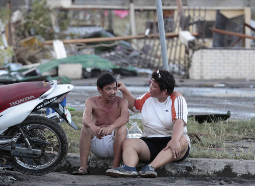 """Residents sit outside their damaged house after powerful Typhoon Haiyan slammed into Tacloban city, Leyte province, central Philippines on Saturday, Nov. 9, 2013. The central Philippine city of Tacloban was in ruins Saturday, a day after being ravaged by one of the strongest typhoons on record, as horrified residents spoke of storm surges as high as trees and authorities said they were expecting a """"very high number of fatalities."""" (AP Photo/Aaron Favila)"""