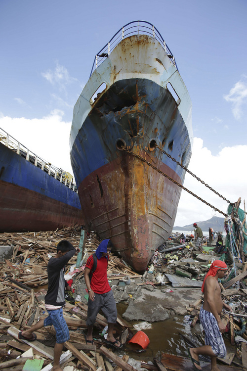 Survivors walk by a large ship after it was washed ashore by strong waves caused by powerful Typhoon Haiyan in Tacloban city, Leyte province, central Philippines on Sunday, Nov. 10, 2013. The city remains littered with debris from damaged homes as many complain of shortages of food and water and no electricity since Typhoon Haiyan slammed into their province. Haiyan, one of the most powerful storms on record, slammed into six central Philippine islands on Friday, leaving a wide swath of destruction and scores of people dead. (AP Photo/Aaron Favila)