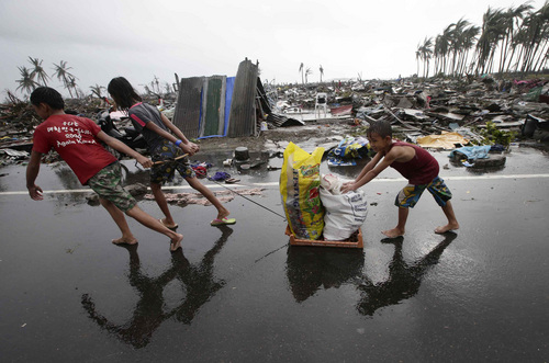 Residents carry relief goods past damaged homes in Tacloban city, Leyte province, central Philippines on Sunday, Nov. 10, 2013. The city remains littered with debris from damaged homes as many complain of shortages of food and water and no electricity since Typhoon Haiyan slammed into their province. Haiyan, one of the most powerful storms on record, slammed into six central Philippine islands on Friday, leaving a wide swath of destruction and scores of people dead. (AP Photo/Bullit Marquez)