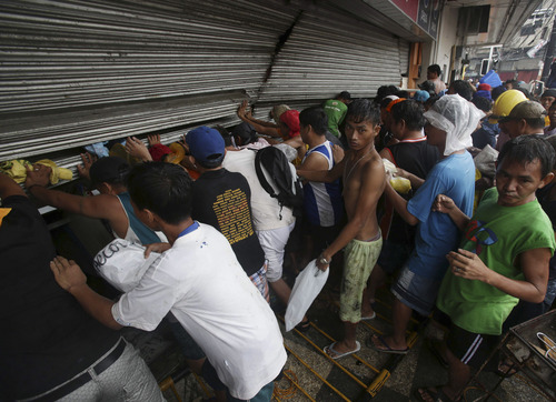 Residents push a shutter to open a small grocery to get food in Tacloban city, Leyte province central Philippines on Sunday, Nov. 10, 2013. The city remains littered with debris from damaged homes as many complain of shortage of food, water and no electricity since the Typhoon Haiyan slammed into their province.  (AP Photo/Aaron Favila)