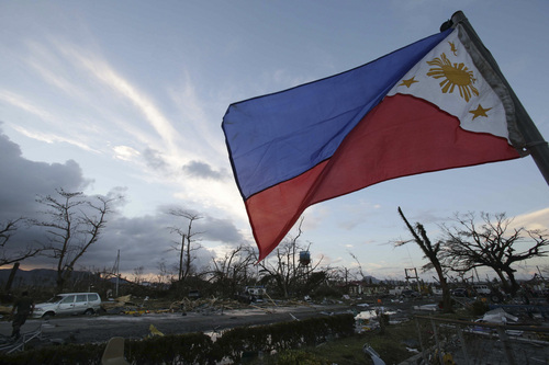 A Philippine flag stands amongst the damage caused after powerful Typhoon Haiyan slammed into Tacloban city, Leyte province, central Philippines on Saturday, Nov. 9, 2013. Rescuers in the central Philippines counted at least 100 people dead and many more injured Saturday, a day after one of the most powerful typhoons on record ripped through the region, wiping away buildings and leveling seaside homes with massive storm surges. (AP Photo/Aaron Favila)