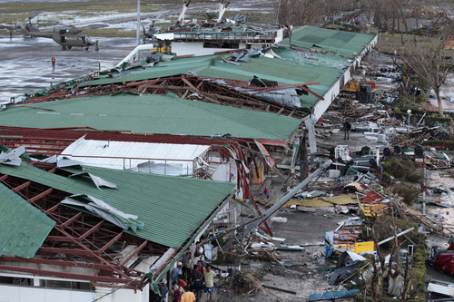 People stay outside the remains of a damaged airport terminal after powerful Typhoon Haiyan slammed into Tacloban city, Leyte province central Philippines on Saturday, Nov. 9, 2013. Rescuers in the central Philippines counted at least 100 people dead and many more injured Saturday, a day after one of the most powerful typhoons on record ripped through the region, wiping away buildings and leveling seaside homes with massive storm surges. (AP Photo/Aaron Favila)