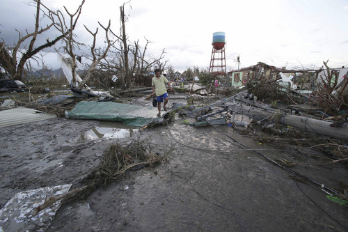 "A resident walks by toppled trees and electric posts after powerful Typhoon Haiyan slammed into Tacloban city, Leyte province, central Philippines on Saturday, Nov. 9, 2013. The central Philippine city of Tacloban was in ruins Saturday, a day after being ravaged by one of the strongest typhoons on record, as horrified residents spoke of storm surges as high as trees and authorities said they were expecting a ""very high number of fatalities."" (AP Photo/Aaron Favila)"