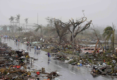 Resident walk past damaged houses in Tacloban city, Leyte province, central Philippines on Sunday, Nov. 10, 2013. The city remains littered with debris from damaged homes as many complain of shortages of food and water and no electricity since Typhoon Haiyan slammed into their province. Haiyan, one of the most powerful storms on record, slammed into six central Philippine islands on Friday, leaving a wide swath of destruction and scores of people dead. (AP Photo/Bullit Marquez)