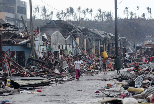 Residents walk past damaged structures caused by typhoon Haiyan,  in Tacloban city, Leyte province central Philippines on Sunday, Nov. 10, 2013. Haiyan, one of the most powerful typhoons ever recorded, slammed into central Philippine provinces Friday leaving a wide swath of destruction and scores of people dead.  (AP Photo/Aaron Favila)