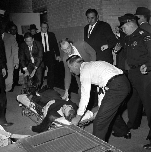 FILE - In this Sunday, Nov. 24, 1963 file photo, Lee Harvey Oswald, accused assassin of President John F. Kennedy, is placed on a stretcher after being shot in the stomach in Dallas. Nightclub owner Jack Ruby shot and killed Oswald as the prisoner was being transferred through the underground garage of Dallas police headquarters. (AP Photo/David F. Smith)