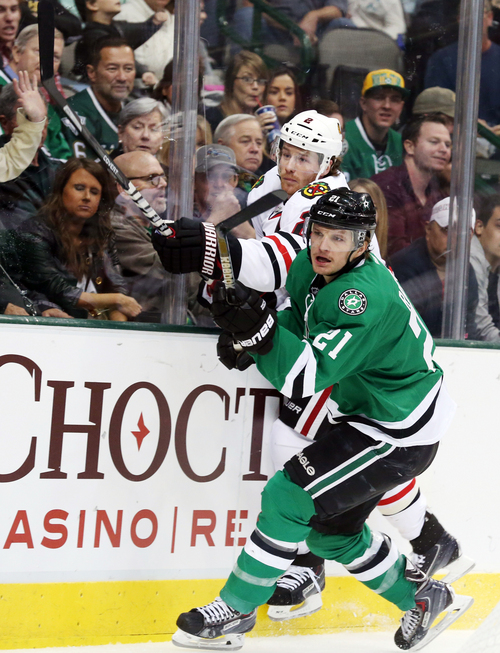 Chicago Blackhawks defenseman Duncan Keith, back, of Canada, and Dallas Stars left wing Antoine Roussel,of France, crash into the boards during the first period of an NHL hockey game Saturday, Nov. 9, 2013, in Dallas, Texas. (AP Photo/Sharon Ellman)