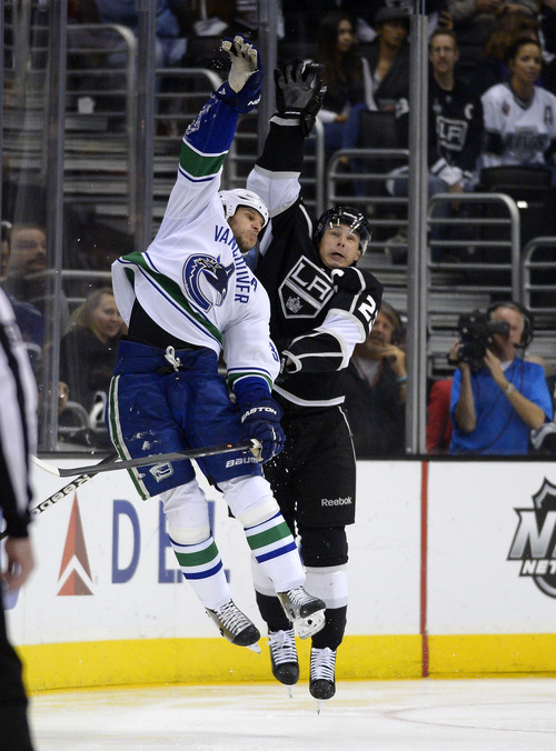 Vancouver Canucks defenseman Kevin Bieksa, left, and Los Angeles Kings right wing Dustin Brown reach for a puck during the third period of an NHL hockey game, Saturday, Nov. 9, 2013, in Los Angeles. The Kings won 5-1. (AP Photo/Mark J. Terrill)
