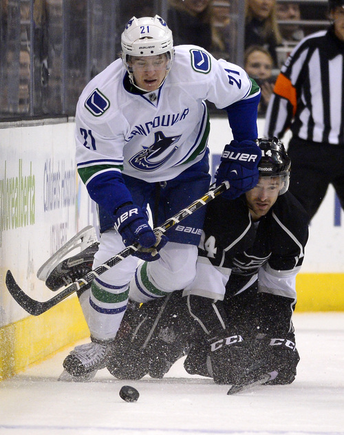 Vancouver Canucks center Zac Dalpe, top, takes the puck as Los Angeles Kings right wing Justin Williams falls during the third period of an NHL hockey game, Saturday, Nov. 9, 2013, in Los Angeles. The Kings won 5-1. (AP Photo/Mark J. Terrill)