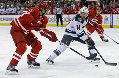Carolina Hurricanes' Tuomo Ruutu (15), of Finland, and Minnesota Wild's Justin Fontaine (14) skate during the second period of an NHL hockey game in Raleigh, N.C., Saturday, Nov. 9, 2013. (AP Photo/Gerry Broome)