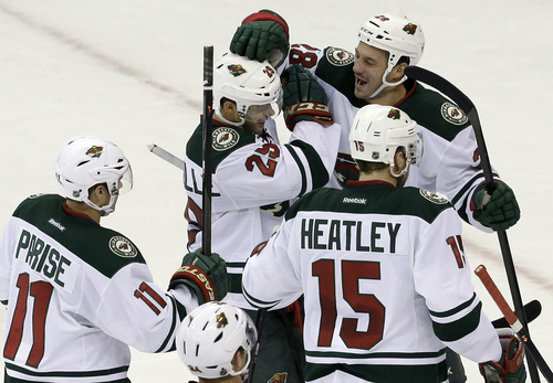 Minnesota Wild's Jason Pominville (29) is congratulated by Zach Parise (11); Dany Heatley (15), of Germany; and Zenon Konopka following Pominville's goal in the shootout of an NHL hockey game in Raleigh, N.C., Saturday, Nov. 9, 2013. Minnesota won 3-2. (AP Photo/Gerry Broome)