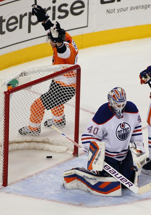 Philadelphia Flyers' Jakub Voracek raises his arms circling the net where a goal by Claude Giroux lays behind Edmonton Oilers goalie Devan Dubnyk during the third period of an NHL hockey game, Saturday, Nov. 9, 2013, in Philadelphia. The Flyers won 4-2. (AP Photo/Tom Mihalek)