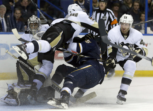 St. Louis Blues' Barret Jackman (5) is hit by Pittsburgh Penguins' Deryk Engelland, second from left, as Penguins goalie Marc-Andre Fleury, left, and Brooks Orpik, right, get in on the play during the second period of an NHL hockey game on Saturday, Nov. 9, 2013, in St. Louis. Engelland was charged with high-sticking on the play. (AP Photo/Jeff Roberson)