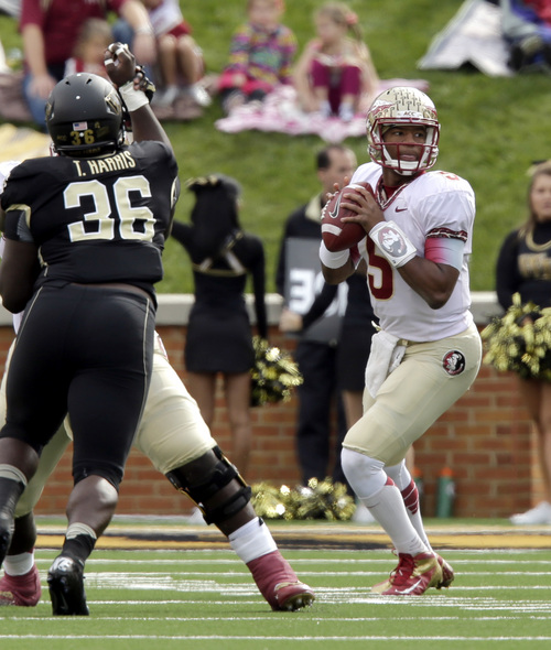 Florida State quarterback Jameis Winston, right, looks to pass  as Wake Forest defensive end Tylor Harris pursues in the first half of an NCAA college football game in Winston-Salem, N.C., Saturday, Nov. 9, 2013. Florida State won 59-3. (AP Photo/Nell Redmond)