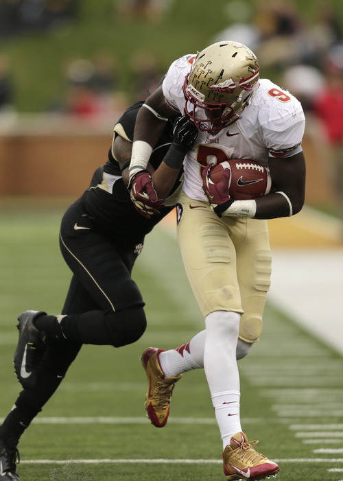 Florida State running back Karlos Williams (9) runs as Wake Forest free safety Anthony Wooding, Jr. grabs his face mask in the second half of an NCAA college football game in Winston-Salem, N.C., Saturday, Nov. 9, 2013. Florida State won 59-3. (AP Photo/Nell Redmond)